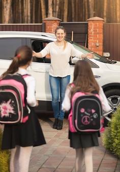 放課後、母親に会う元気な女の子2人