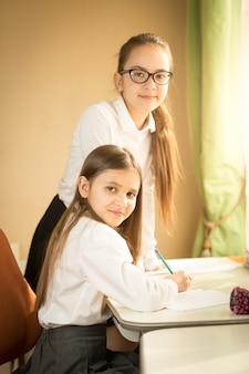 Two cheerful girls  in school uniform posing behind desk