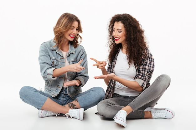 Two cheerful girls sitting on the floor together and having fun over whit wall