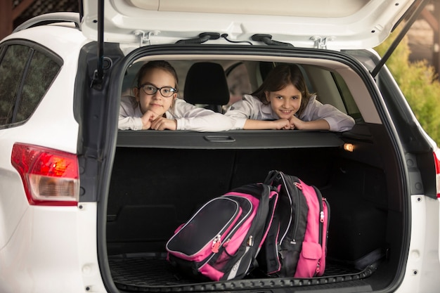 Две веселые девушки сидят в машине перед школой