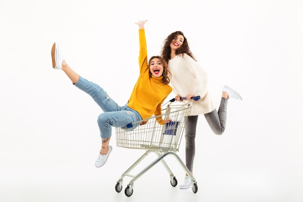 Two cheerful girls in sweaters having fun together with shopping trolley