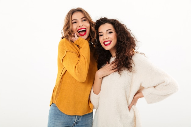 Two cheerful girls in sweaters posing together  over white wall