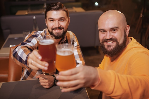 Two cheerful handsome men smiling to the camera, clinking their beer glasses