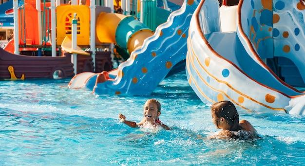 두 쾌활한 행복한 여자 자매는 오랫동안 기다려온 편안한 휴가에 맑은 맑은 물과 함께 수영장에서 재미와 웃음