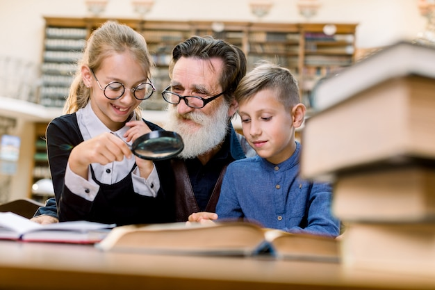 Two cheerful kids, boy and girl with magnifying glass glass listening to interesting book story from their handsome bearded grandfather or school teacher, sitting together in old library.
