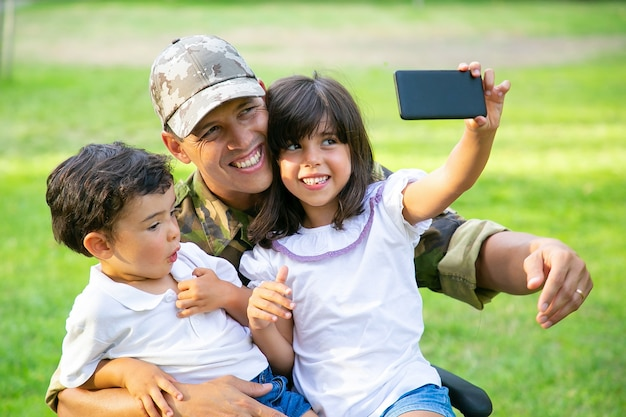 Two cheerful kids sitting on dads lap and taking selfie on cell. disabled military man walking with kids in park. veteran of war or disability concept