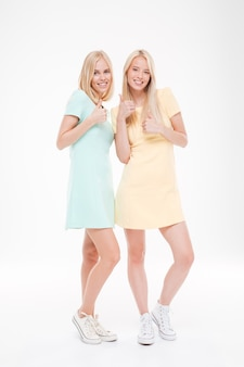 Two cheerful ladies makes cool gesture isolated over white wall.