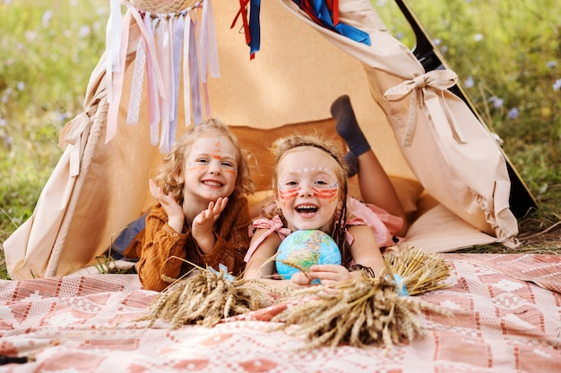 Two cheerful little girls with native americans make up on their faces inside wigwam are having fun outdoors in summer