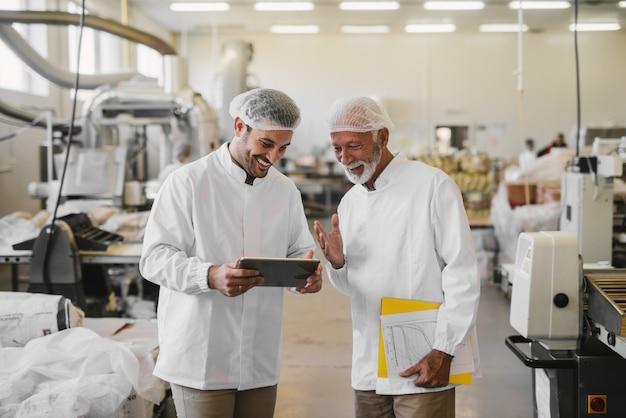 Два жизнерадостных коллег-мужчин в стерильной одежде стоят на пищевой фабрике и смотрят торговые документы на цифровом планшете.