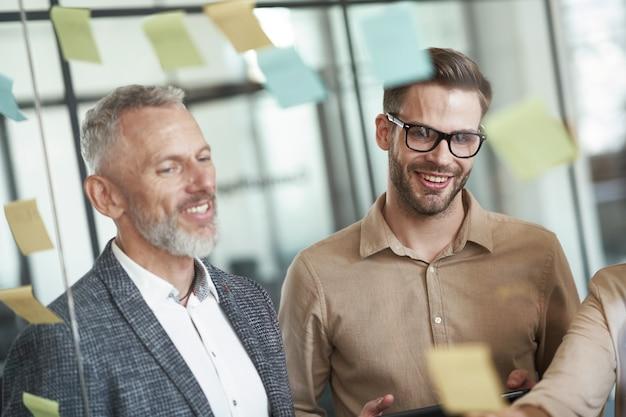 Два веселых коллеги-мужчины, стоящие в современном офисе и смотрящие на красочные липкие заметки на