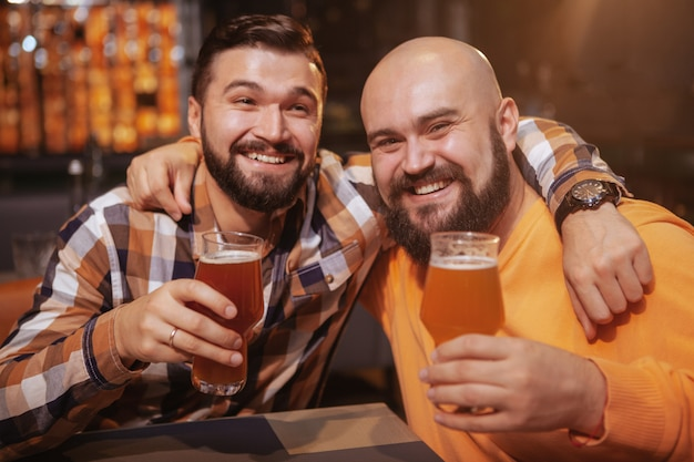 Two cheerful male friends embracing, drinking beer together at the pub