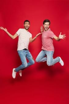 Двое веселых друзей-мужчин прыгают изолированно через красную стену