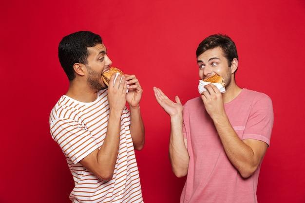 두 쾌활한 남자 친구는 햄버거를 먹고, 붉은 벽 위에 고립 된 서