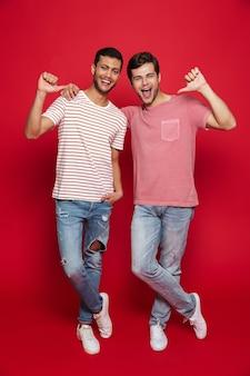 Двое веселых друзей-мужчин стоят изолированно над красной стеной и указывают на себя