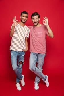 Двое веселых друзей-мужчин стоят изолированно над красной стеной, показывая хорошо