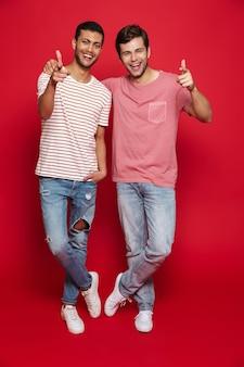 Двое веселых друзей-мужчин стоят изолированно над красной стеной