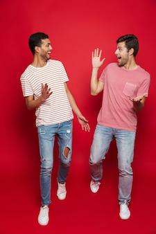 Двое веселых друзей-мужчин гуляют изолированно по красной стене
