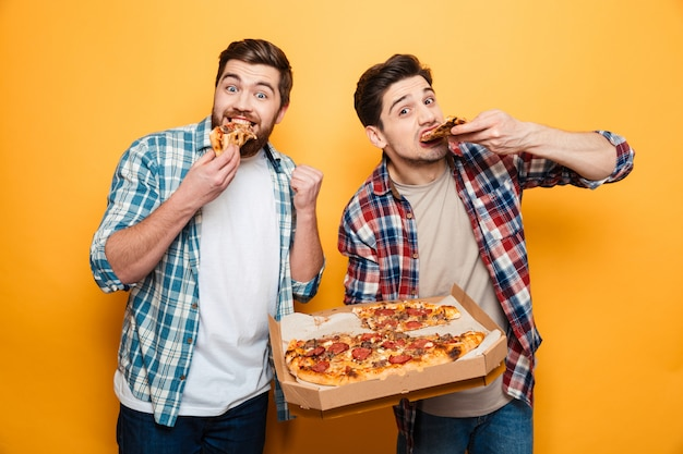 Two cheerful men in shirts eating pizza  over yellow wall