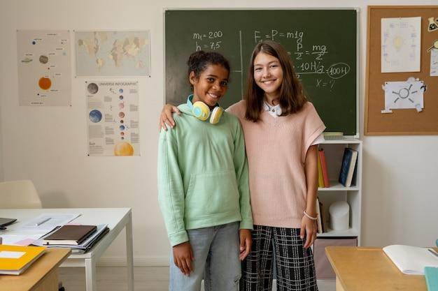 칠판에 서 있는 캐주얼웨어를 입은 두 명의 쾌활한 다인종 여학생
