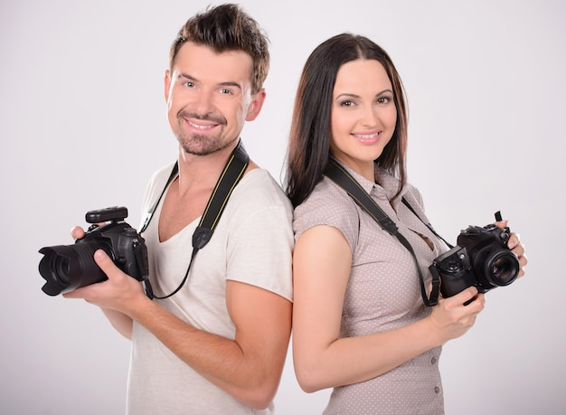 Two cheerful photographers holding cameras.