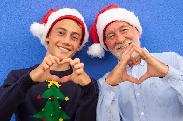 두 명의 쾌활한 산타클로스가 파란 벽에 기대어 있고, 할아버지와 10대 손자가 손으로 하트를 만들고 있습니다. 가족, 사랑과 재미의 개념