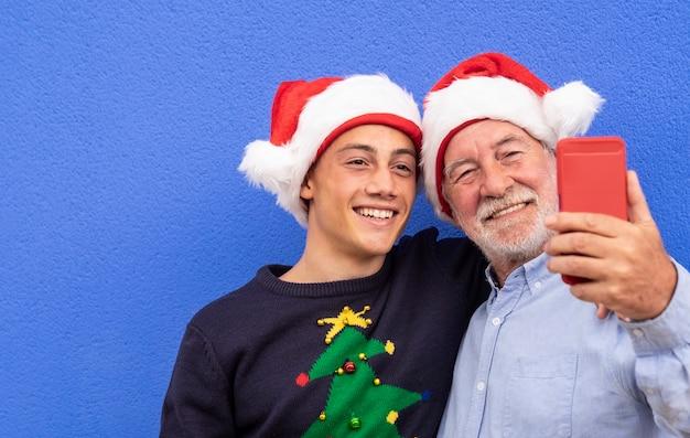 Два веселых санта-клауса обнимают друг друга у синей стены, дедушка с внуком-подростком улыбаются, делая селфи на смартфон. концепция современной и технологической семьи