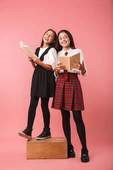 ピンクの壁に隔離された制服を着て、本を持っている2人の陽気な女子校生