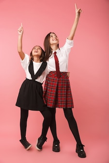 Two cheerful school girls wearing uniform standing isolated over pink wall, pointing fingers