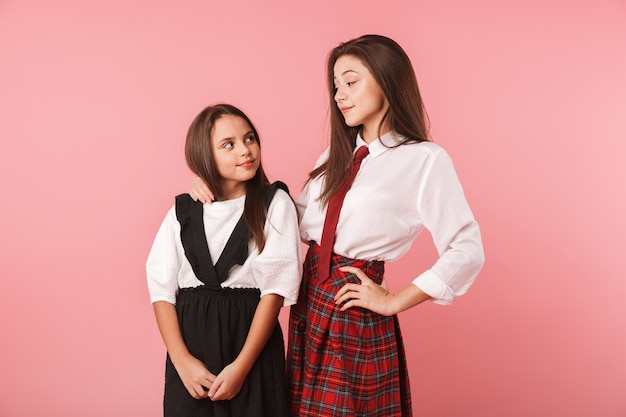 Two cheerful school girls wearing uniform standing isolated over pink wall