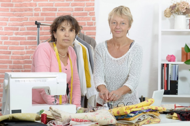 Two cheerful seamstresses working together in their  workshop