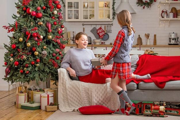 2人の陽気な姉妹がクリスマスツリーの近くに家に座って、クリスマスにお互いに祝福し、贈り物をします。