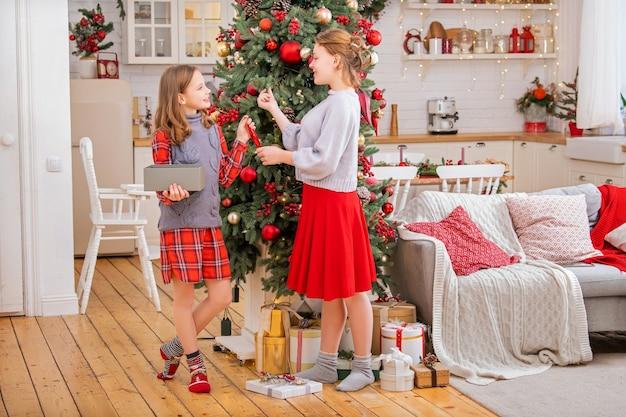 2人の陽気な姉妹のティーンエイジャーが部屋の自宅でクリスマスツリーを飾ります。