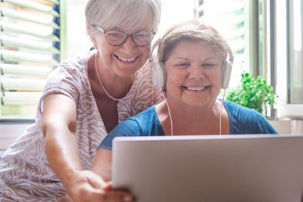 同じラップトップを使用して笑っている2人の陽気な姉妹。自宅で魅力的な成熟した女性