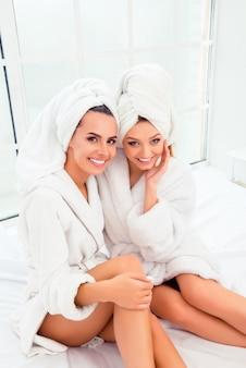 入浴後のベッドに座っている完璧な肌を持つ2人の陽気な姉妹