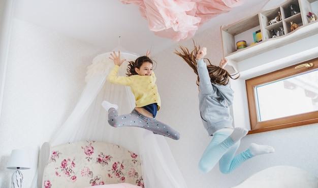 寝室のベッドに飛び乗って、自宅の屋内で2人の陽気な小さな女の子の姉妹。