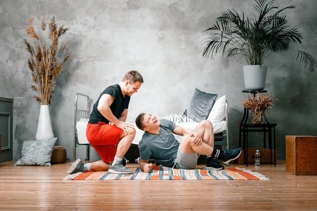 友人の2人の陽気なスポーツマンが寝室で自宅でトレーニングをしています。若い男は家でスポーツに出かけ、足を引っ張ったが、それでも楽しんでいる。