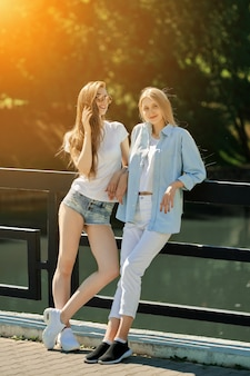 Two cheerful student girls standing on the bridge in hot sunny day