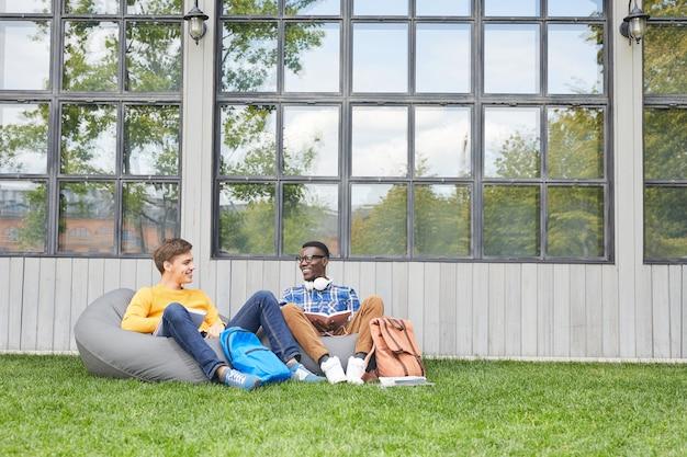 屋外でリラックスした2人の陽気な学生