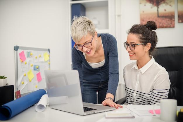 Два веселых успешных бизнес-леди в офисе, работая вместе над некоторыми новыми идеями.