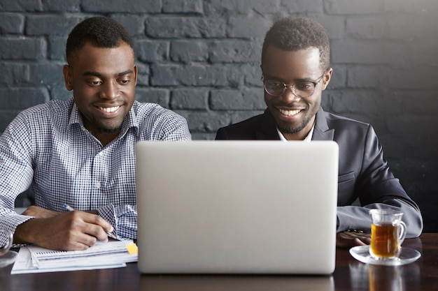Two cheerful successful young african american businessmen sitting in modern office interior in front of open laptop computer, looking at screen with happy smiles, discussing business plans and ideas