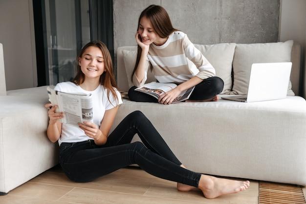 雑誌を読んでソファに家で座っている2人の陽気なティーンエイジャーの女の子の友人