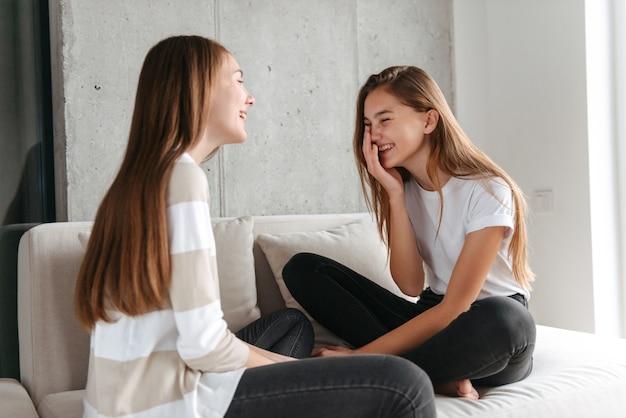 소파에 집에 앉아있는 동안 얘기 두 명랑 십대 여자 친구