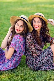 Две веселые близнецы сидят на зеленом лугу и наслаждаются временем вместе.