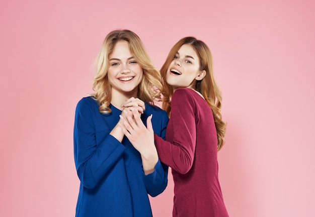 Two cheerful women in dresses are standing next to friendship emotions pink background