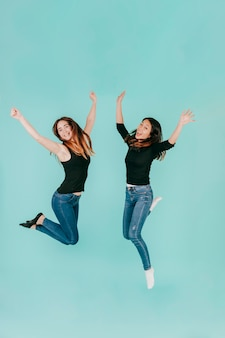 Two cheerful women jumping high