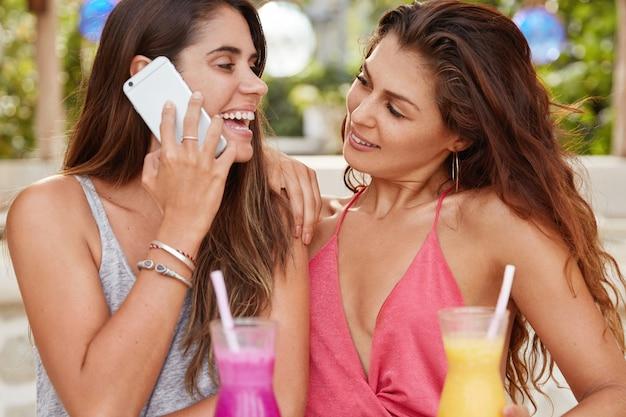 두 명의 쾌활한 여성 레즈비언이 칵테일과 함께 야외 카페에서 자유 시간을 보냅니다.