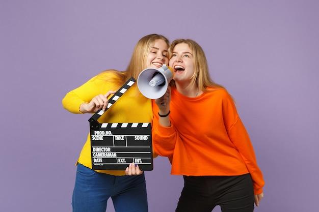 Две веселые молодые блондинки сестры-близнецы держат классический черный фильм, делая с 'хлопушкой', кричат на мегафон, изолированном на фиолетово-синей стене. концепция семейного образа жизни людей.