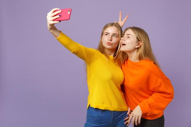 パステルバイオレットブルーの壁に隔離された携帯電話でselfieショットをしているカラフルな服を着た2人の陽気な若いブロンドの双子の姉妹の女の子。人々の家族のライフスタイルの概念。