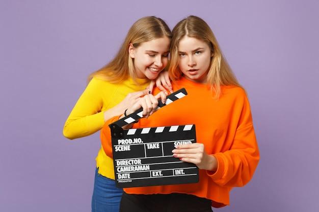 화려한 옷을 입고 두 쾌활한 젊은 금발 쌍둥이 자매 소녀는 보라색 파란색 벽에 고립 된 clapperboard를 만드는 고전적인 검은 영화를 개최합니다. 사람들이 가족 라이프 스타일 개념.
