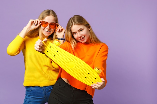 鮮やかな服を着た2人の陽気な若い金髪の双子の姉妹の女の子、ハートの眼鏡はパステルバイオレットブルーの壁に分離された黄色のスケートボードを保持します。人々の家族のライフスタイルの概念。